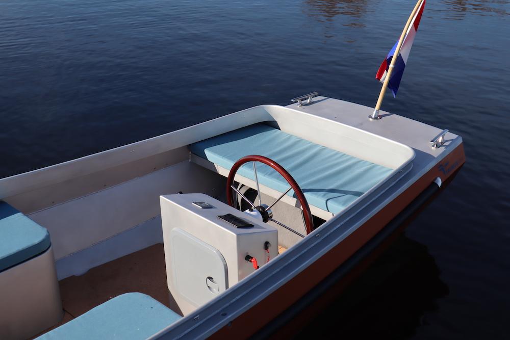 Binnenkant van een elektrische boot met kussens en stuurinrichting